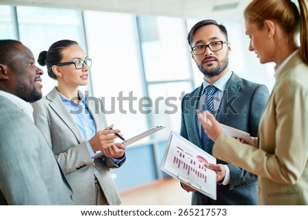 Group of elegant colleagues communicating at meeting - stock photo