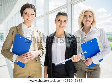 Group of elegant female office workers standing in line and smiling to camera. - stock photo