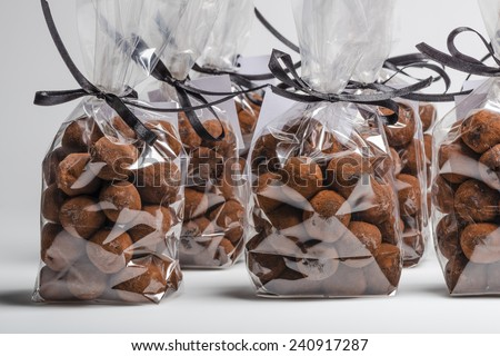Group of elegant plastic bags with black ribbon of Christmas chocolate truffles in a row. Shooting on white background in studio. - stock photo