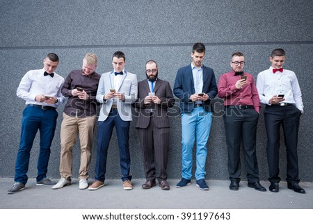 Group of elegant young businessmen standing against the wall and checking their mobile phones. - stock photo
