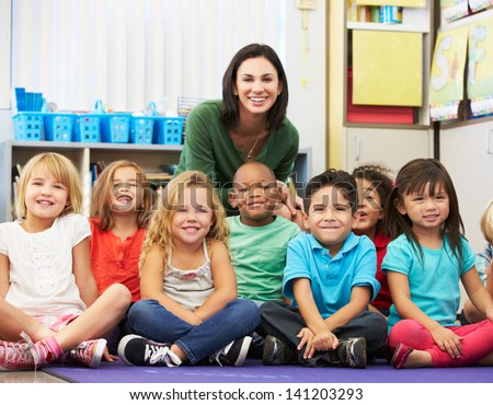 Group of Elementary Pupils In Classroom With Teacher - stock photo
