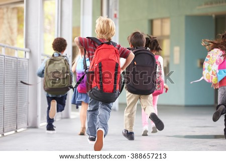 Group of elementary school kids running at school, back view - stock photo