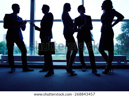 Group of employees having business meeting against window - stock photo