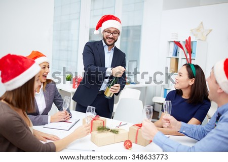 Group of employees looking at their colleague opening bottle of champagne - stock photo