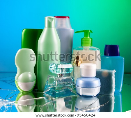 Group of empty cosmetic bottles on beautiful green and blue mirror - stock photo