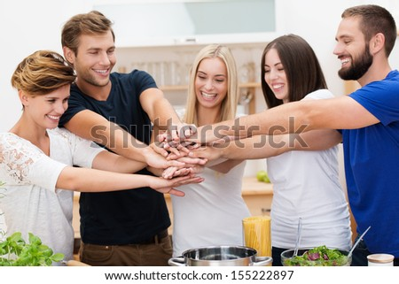 Group of enthusiastic multicultural young friends with happy smiles standing in the kitchen placing their hands in a stack denoting cooperation and teamwork - stock photo