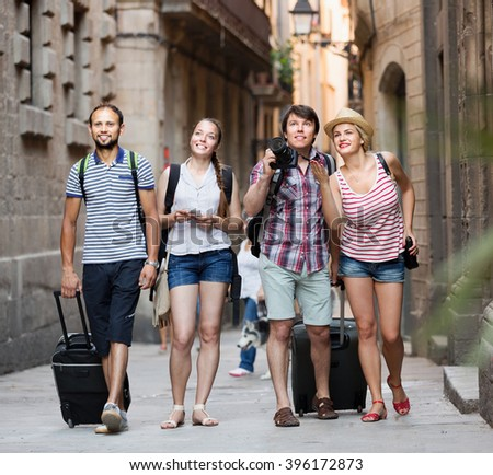 Group of european tourists walking the street with luggage at vacation - stock photo