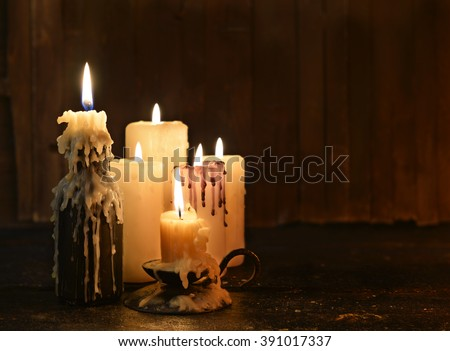 Group of evil candles burning in the darkness and copy space on wooden background. Black magic ritual or scary halloween rite.  - stock photo