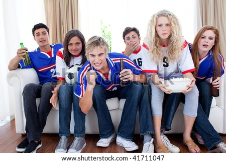 Group of excited and happy teenagers watching a football match at home - stock photo