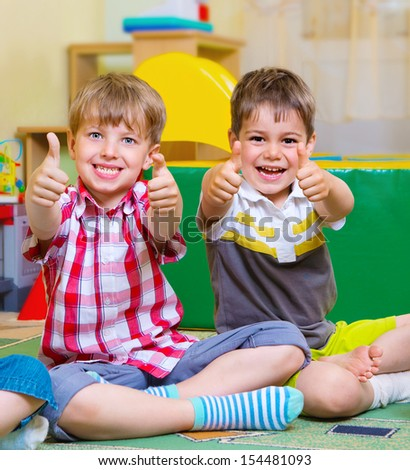 Group of excited children holding thumbs up - stock photo