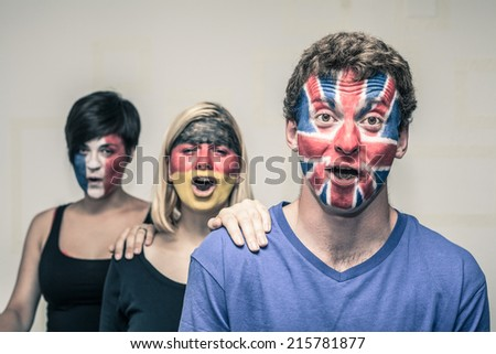 Group of excited people with painted flags on their faces shouting. - stock photo