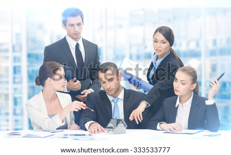 Group of executives debating while sitting at the table, blue background. Concept of teamwork and cooperation - stock photo