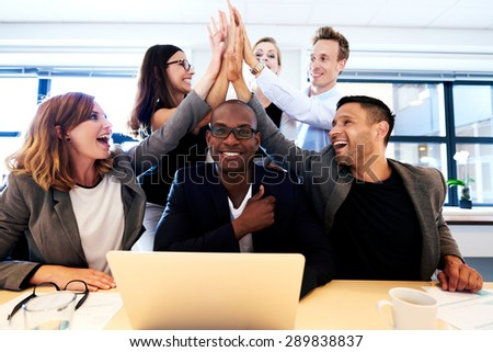 Group of executives smiling and group high fiving over black colleague's head - stock photo