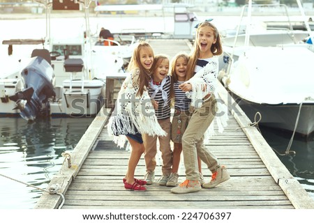 Group of fashion kids wearing navy clothes in marine style having fun in the sea port - stock photo