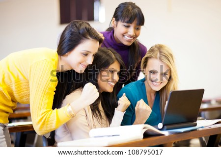 group of female college students cheering a game on laptop - stock photo