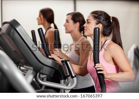 Group of female friends doing some cardio in an elliptical trainer in a gym - stock photo