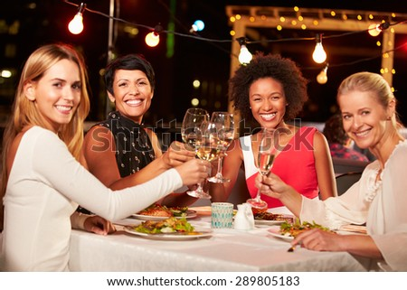 Group of female friends eating dinner at rooftop restaurant - stock photo