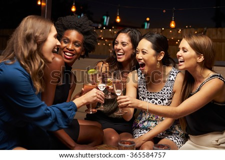 Group Of Female Friends Enjoying Night Out At Rooftop Bar - stock photo