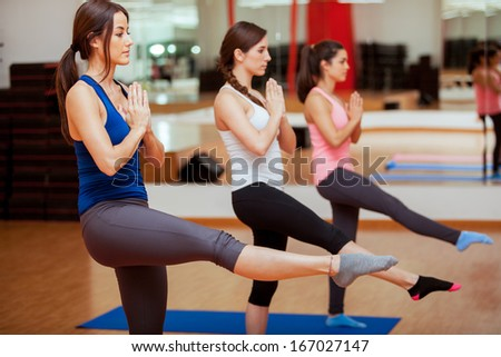 Group of female friends relaxing and meditating during their yoga class - stock photo