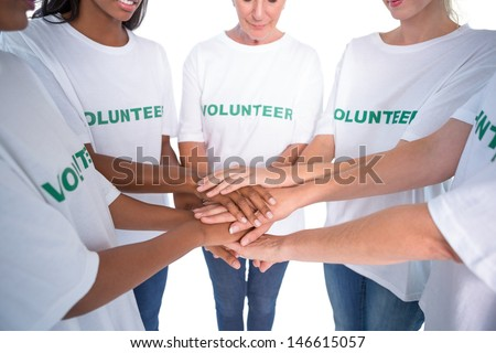 Group of female volunteers with hands together on white background - stock photo