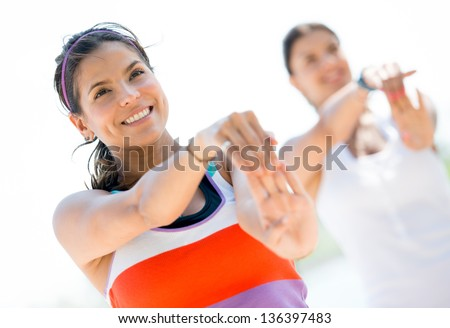 Group of fit women stretching outdoors and smiling - stock photo
