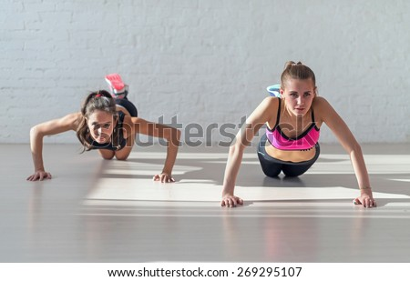 Group of fit women warming up and doing push ups working at gym fitness, sport, training, diet and lifestyle concept. - stock photo
