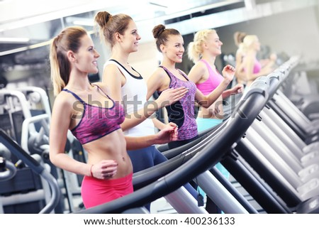 Group of fit women working out on treadmill in gym - stock photo