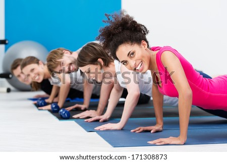 Group of fit young people doing push ups while working out in a class in the gym with focus to a beautiful vivacious young African American woman in the foreground - stock photo