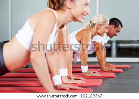 group of fitness people doing push ups in gym - stock photo