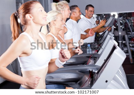 group of fitness people exercising with treadmill in gym - stock photo