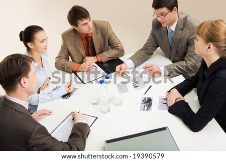 Group of five businesspeople discussing different questions gathered together around the table - stock photo