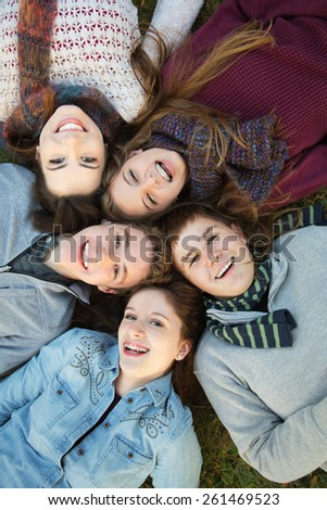 Group of five Caucasian teenagers laying down on grass together - stock photo
