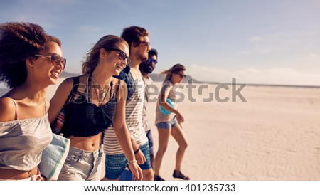Group of five friends walking on the beach. Two young men and three young women on a summer beach vacation. - stock photo