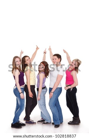 Group of five girls in a row pointing to copy space - stock photo