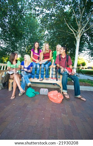 Group of five laughing high school girls and one boy sitting on a bench holding books. Vertically framed photo. - stock photo