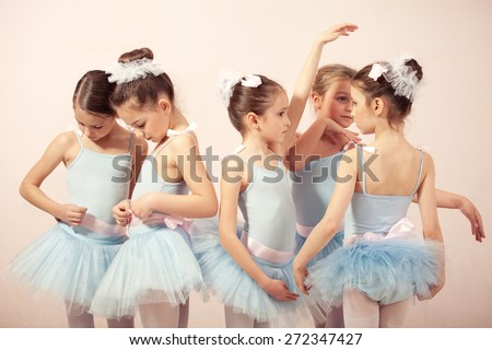 Group of five little ballerinas posing together and practicing for performance. They are good friend and amazing dance performers - stock photo