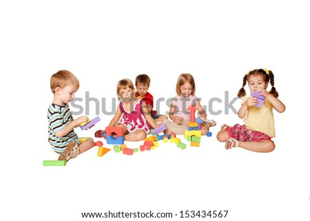 Group of five little children playing and building tower and the city of blocks together. Isolated on white background. - stock photo