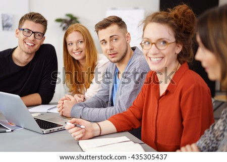 Group of five male and female coworkers with cheerful expressions around laptop computer at meeting table - stock photo