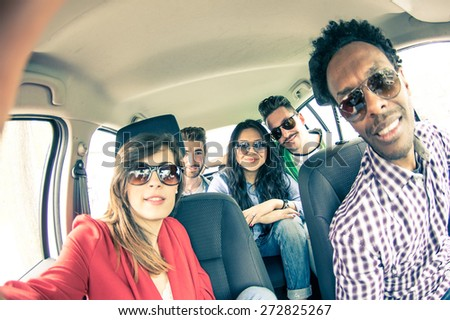 Group of five people driving to vacation and taking a selfie in the car - Happy people of of diverse ethnics in an automobile - Friends renting a car and driving somewhere - stock photo