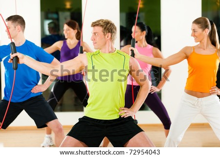 Group of five people exercising with a bar to strengthen the intrinsic muscles in gym or fitness club - stock photo