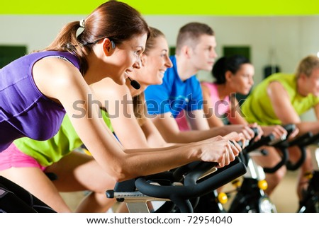 Group of five people in gym or fitness club exercising their legs doing cardio training - stock photo