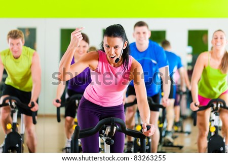 Group of five people - men and women - in gym or fitness club exercising their legs doing cardio training; the trainer is in front - stock photo