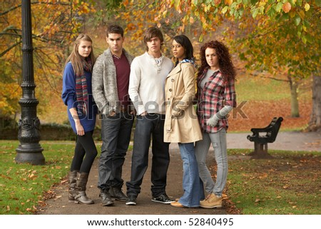 Group Of Five Teenage Friends Having Fun In Autumn Park - stock photo