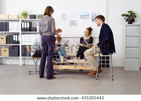Group of five young adult male and female business people in casual clothing seated around small table in bright white office with bulletin board and shelving on walls - stock photo