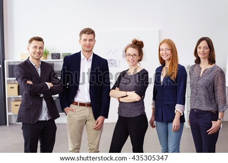 Group of five young male and female smiling business people standing beside each other with white wall behind them - stock photo