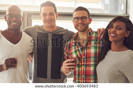 Group of four Black, Caucasian and Hispanic happy adult friends wearing casual clothing and holding drinks while embracing each other in office with large bright window - stock photo