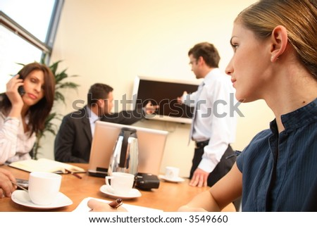 group of four business people at work. one woman is calling on a phone,another is making notes,two men are talking about data at tv screen. - stock photo