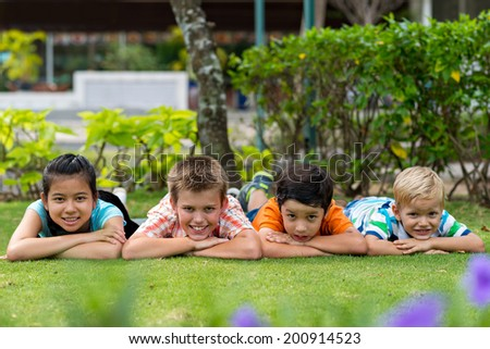 Group of four cheerful kids lying on the stomachs on the grass in the park - stock photo