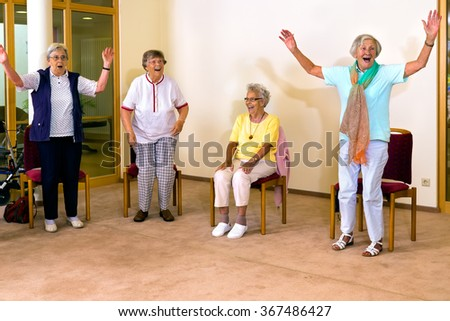 Group of four cheering senior women practicing light aerobic exercises with chairs for fitness class indoors - stock photo