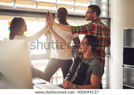Group of four diverse men and women in casual clothing celebrating business accomplishments in office near desk and bright window - stock photo